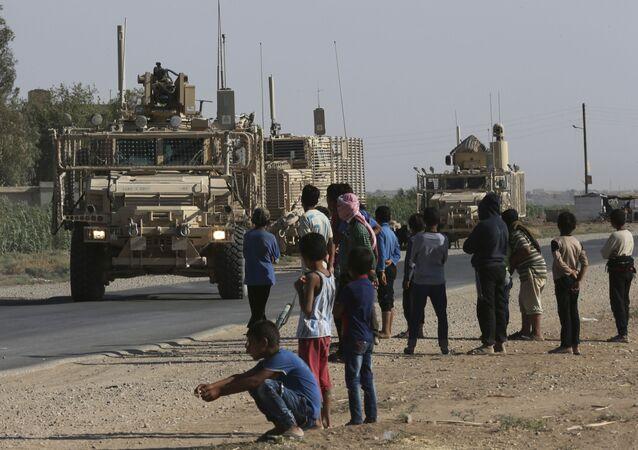 Crianças e jovens sírios olham para a passagem de um comboio de veículos blindados dos EUA em uma estrada que liga a Raqqa, no nordeste da Síria, em 26 de julho de 2017