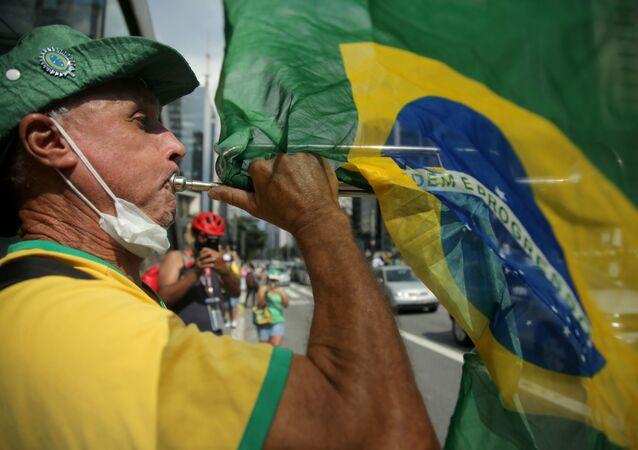 Manifestante participa de ato contra medidas de combate à COVID-19 em São Paulo, 14 de março de 2021