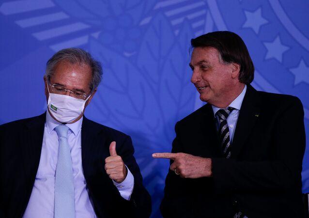 Em Brasília, o presidente brasileiro, Jair Bolsonaro (à direita) aponta na direção do ministro da Economia, Paulo Guedes (à esquerda), que gesticula, em 26 de novembro de 2020