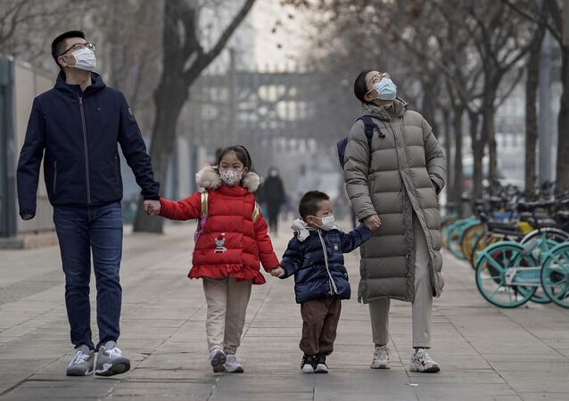 Um casal e seu filho em uma rua de Pequim usando máscaras faciais para ajudar a conter a disseminação do coronavírus