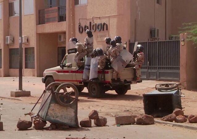 Policiais de choque dirigem-se a um grupo de manifestantes em um posto de controle improvisado, em Niamey, Níger, 24 de fevereiro de 2021.