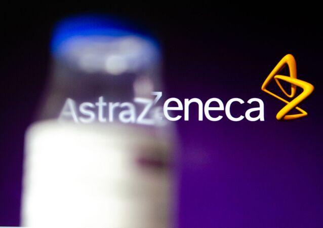 Frasco da vacina de Oxford/AstraZeneca contra a COVID-19 com a logo da empresa ao fundo