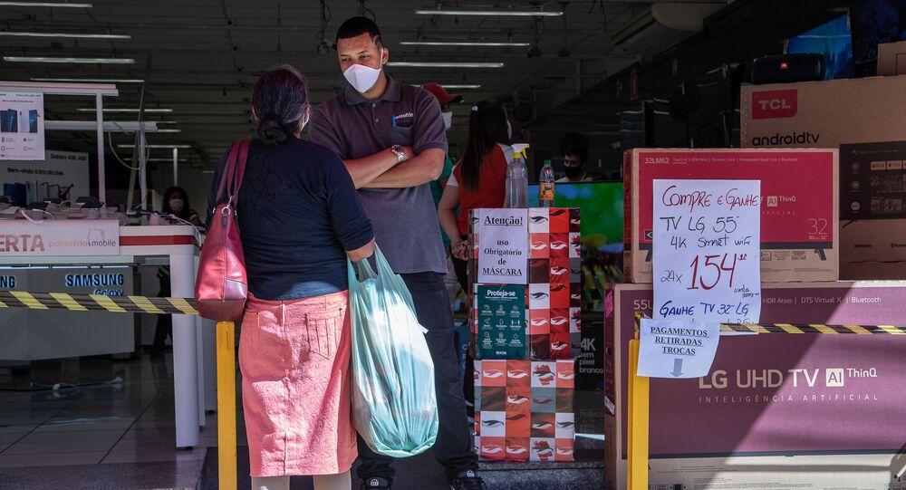 Funcionário com máscara de proteção e álcool em gel em loja de eletrônicos em Marília, interior de São Paulo.