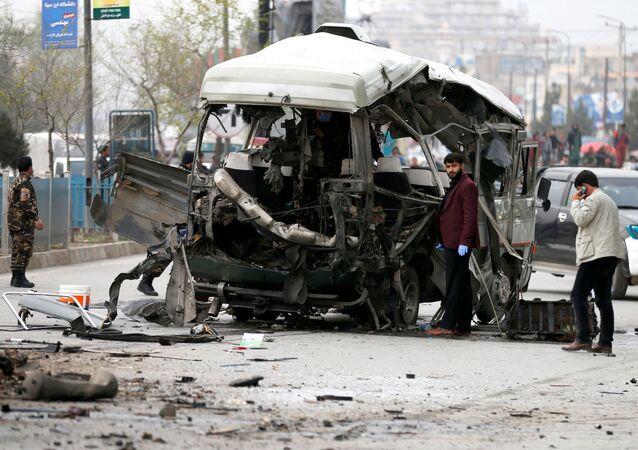 Autoridades afegãs inspecionam um micro-ônibus danificado após uma explosão em Cabul, Afeganistão, em 15 de março de 2021