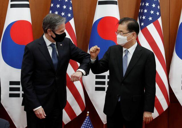 O secretário de Estado, Antony Blinken, e o chanceler sul-coreano, Chung Eui-yong, batem cotovelos durante encontro em 18 de março de 2021