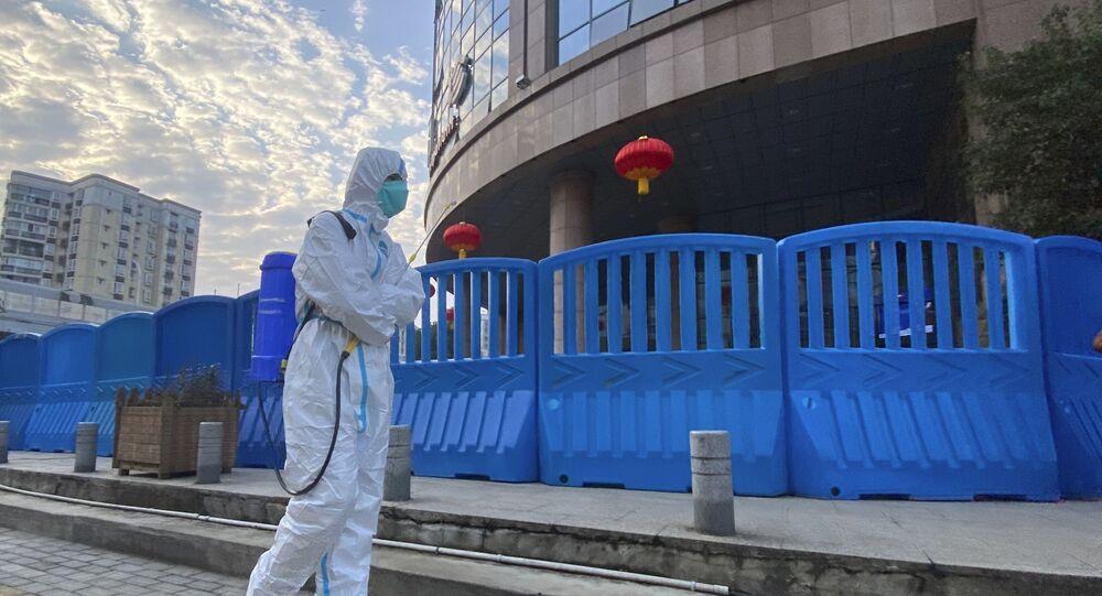 Trabalhador desinfeta do lado de fora do Centro Hospitalar de Wuhan, na China