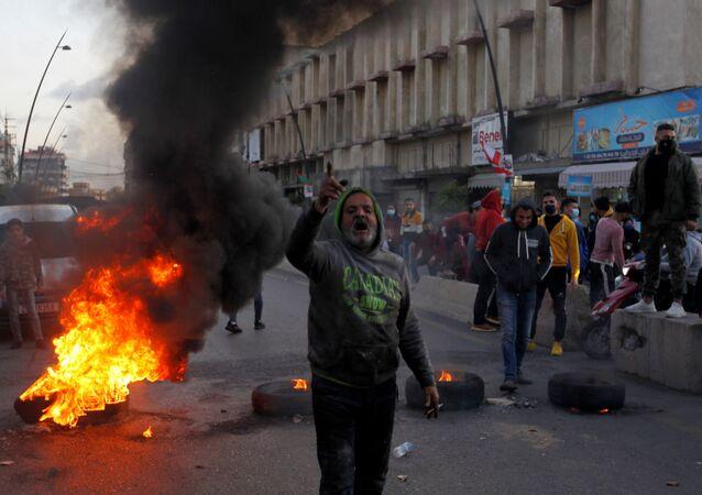 Manifestante gesticula durante um protesto contra a queda da libra libanesa e as crescentes dificuldades econômicas, em Sidon, Líbano, 8 de março de 2021.