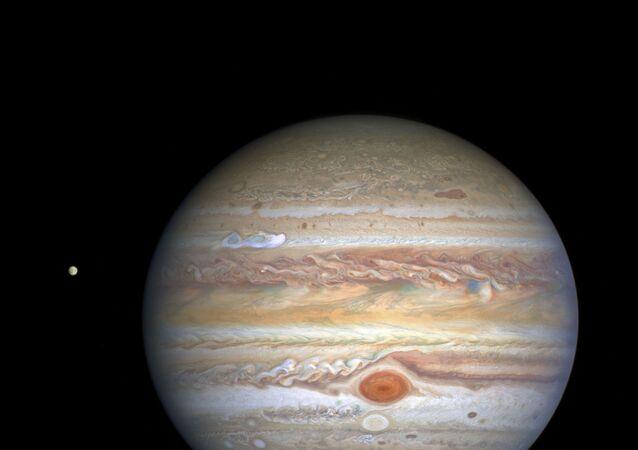Planeta Júpiter e, à esquerda, sua lua Europa