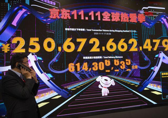 Homem passa por painel eletrônico que mostra 250 bilhões de yuans de vendas acumuladas em um centro de comando na sede da varejista online JD.com em Pequim, China
