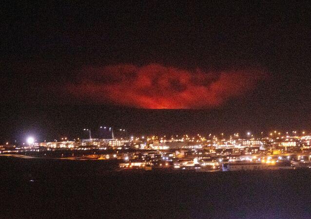 Uma erupção vulcânica é vista atrás, perto de Fagradalsfjall, uma montanha na Península de Reykjanes, na Islândia, em 19 de março de 2021