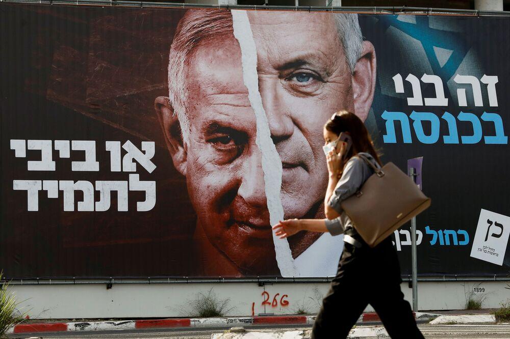 Mulher passa por uma faixa de campanha eleitoral do partido Azul e Branco representando seu líder, o ministro da Defesa Benny Gantz, ao lado do primeiro-ministro israelense Benjamin Netanyahu