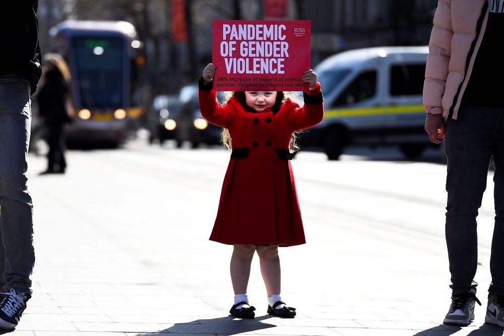 Menina segurando nas mãos um cartaz durante uma ação de protesto contra a violência, Dublin, Irlanda