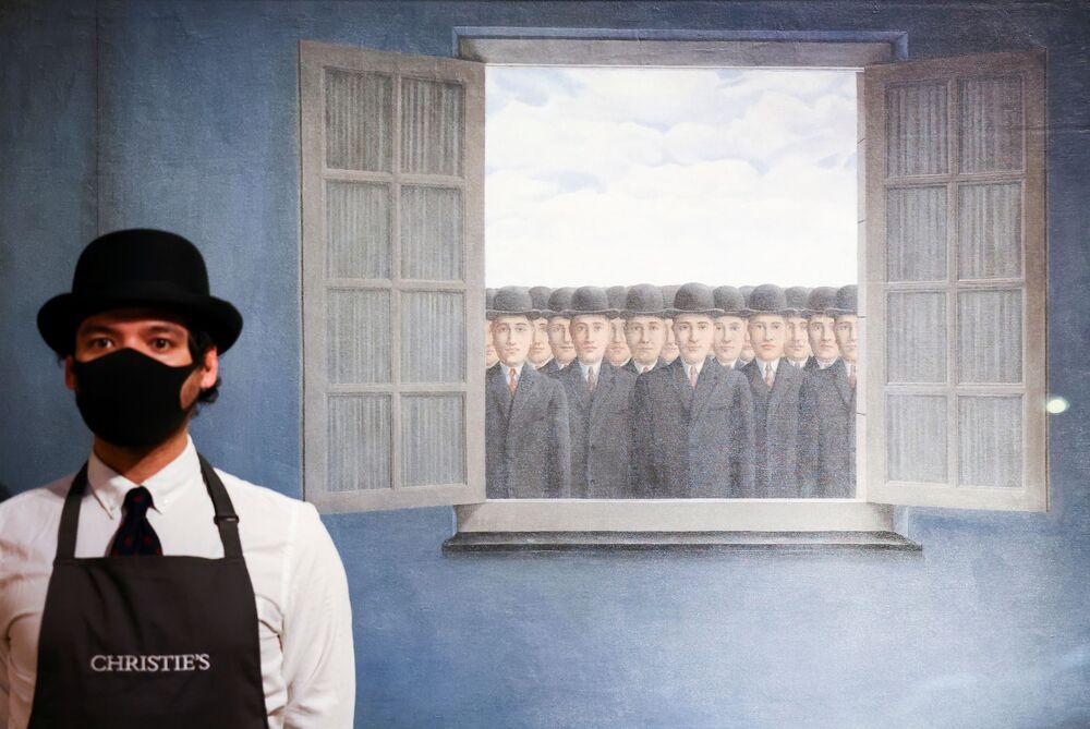 Assistente da galeria posa ao lado de uma obra do artista René Magritte denominada Le Mois des Vendanges durante uma sessão fotográfica