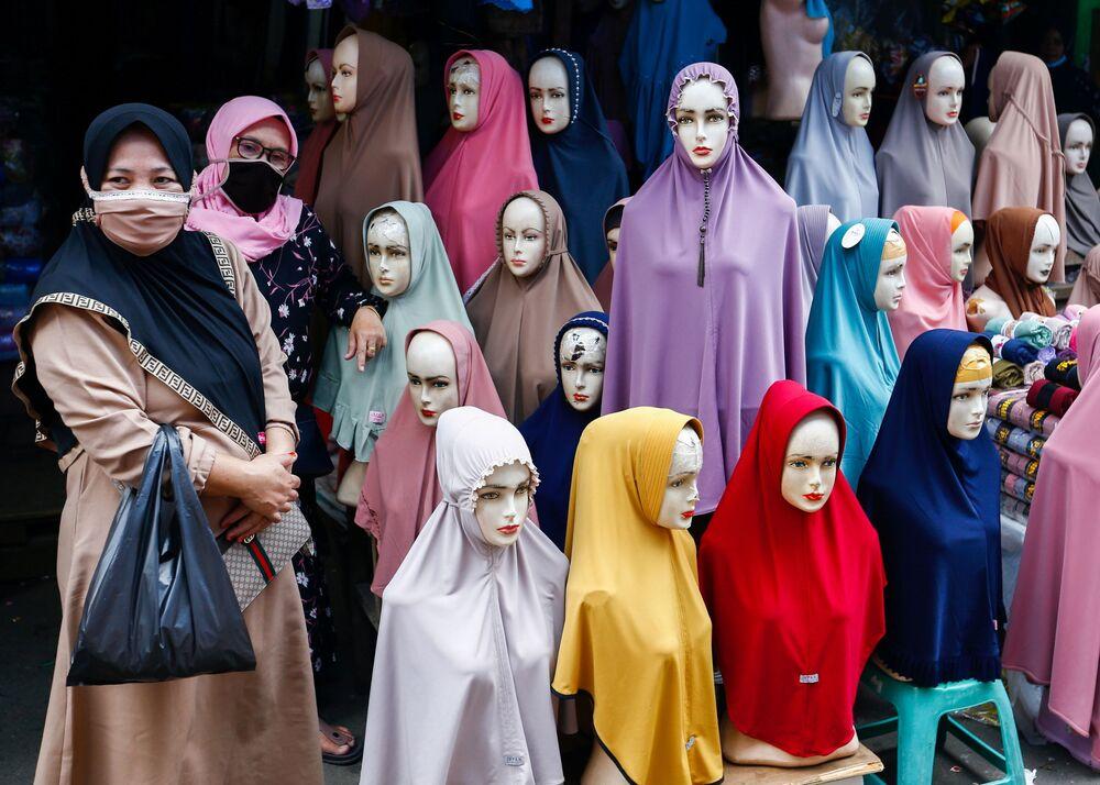 Mulheres usando máscaras protetoras ao lado de manequins com hijab no mercado têxtil de Tanah Abang, Indonésia