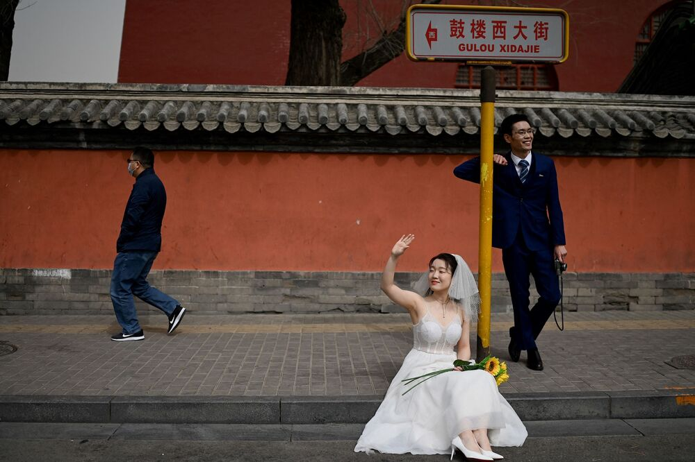 Recém-casados posam durante sessão fotográfica em frente à Torre do Tambor em Pequim, China