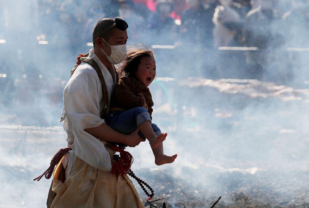 Monge budista carrega bebê durante um festival de caminhada sobre fogo no Japão