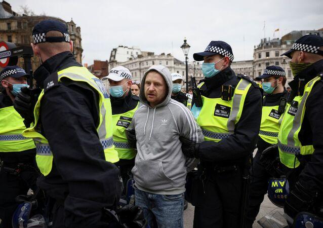 Homem é preso pela policial em protesto contra medidas de isolamento para conter pandemia do coronavírus em Londres