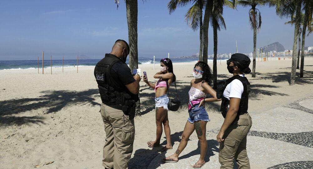 Jovens são abordadas por guardas municipais na praia do Leme, Zona Sul do Rio de Janeiro, neste sábado, 20 de março de 2021, em meio às novas medidas de restrição adotadas na cidade