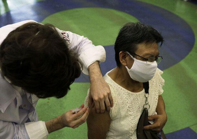 Idosa é vacinada contra a COVID-19 na Fundação Planetário da Cidade do Rio de Janeiro, 18 de março de 2021