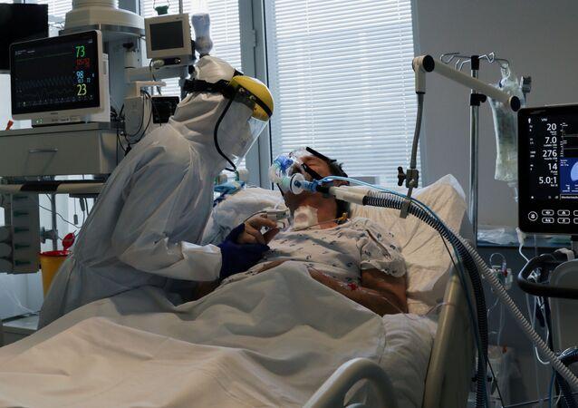 Em Vila Real, Portugal, um profissional de saúde atende um paciente internado com COVID-19 em uma UTI, em 22 de fevereiro de 2021