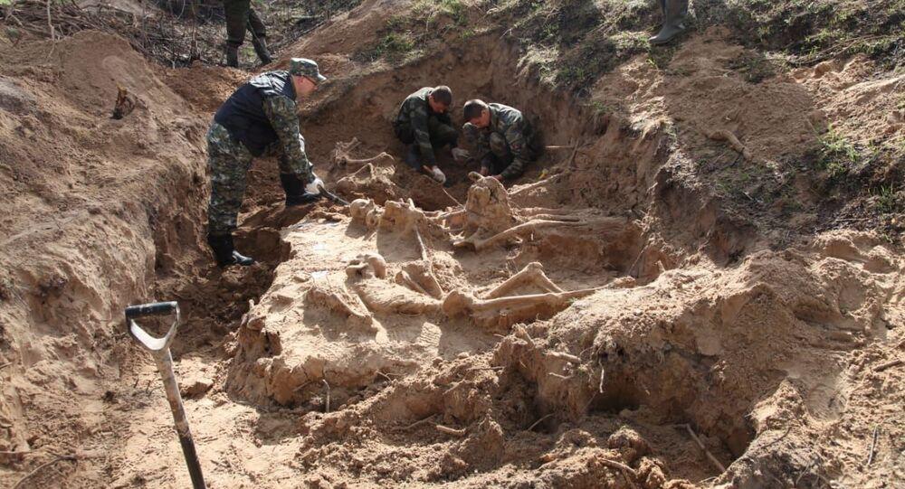 Escavação do local onde foram enterrados os civis massacrados pelos nazistas em Zhestyanaya Gorka
