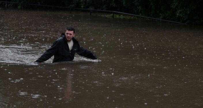 Homem caminha por rua inundada em Sydney, na Austrália, após as fortes chuvas que atingiram o estado de Nova Gales do Sul