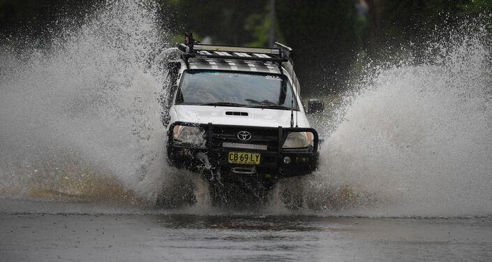 Carro tenta atravessar estrada inundada em Nova Gales do Sul, no sudeste da Austrália