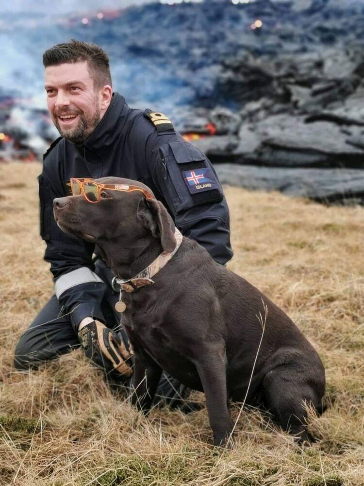 Hrannar Sigurdsson, mecânico de aeronaves do esquadrão de helicópteros da Guarda Costeira islandesa, posa para foto com um cachorro encontrado perto da erupção de vulcão na península de Reykjanes na Islândia, 20 de março de 2021