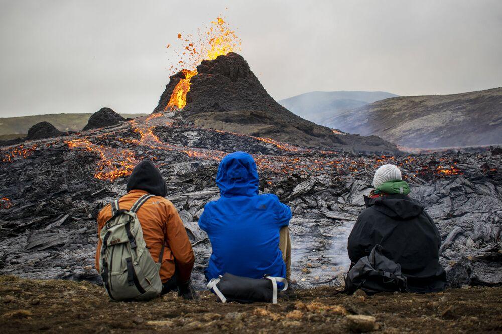 Pedestres observam erupção de vulcão 40 quilômetros a oeste da capital Reiquiavique, na Islândia, 21 de março de 2021