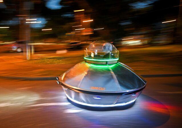 Homem mascarado dirige carro de brinquedo em forma de OVNI em um parque em Cali, Colômbia