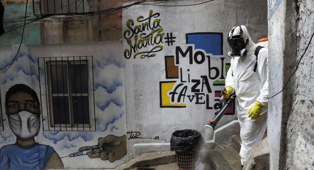 No Rio de Janeiro, um voluntário desinfeta vielas na favela de Santa Marta, em meio à pandemia da COVID-19, em 13 de março de 2021