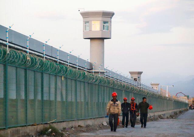 Os trabalhadores caminham pela cerca do perímetro do que é oficialmente conhecido como um centro de educação de habilidades vocacionais em Dabancheng, na Região Autônoma Uigur de Xinjiang, China, 4 de setembro de 2018