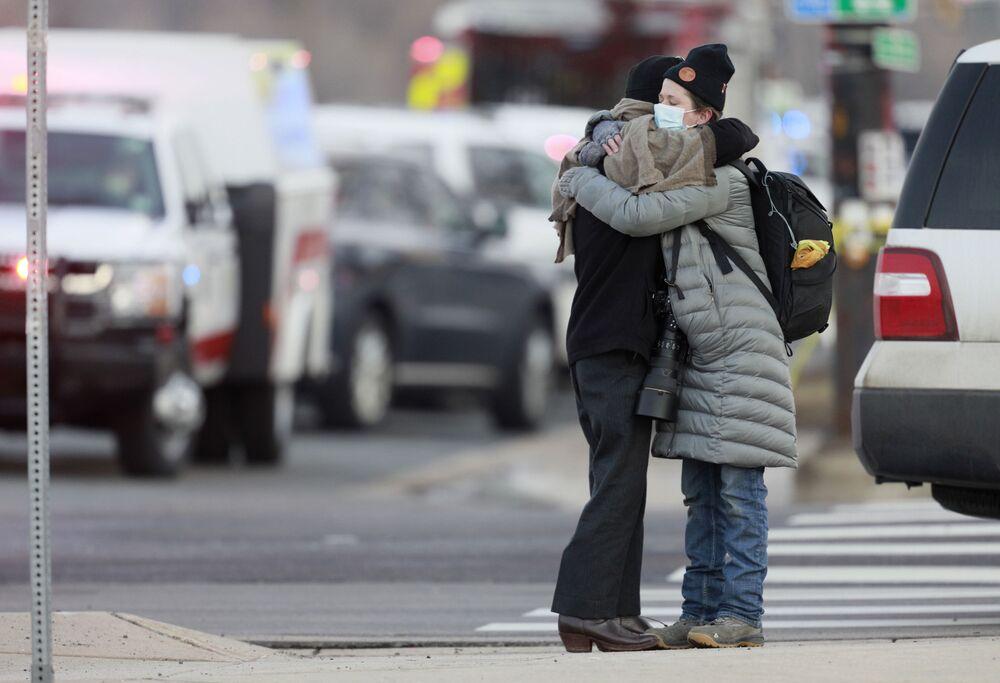 Mulheres se abraçam perto do supermercado King Soopers, onde ocorreu tiroteio, Boulder, Colorado, EUA, 22 de março de 2021.