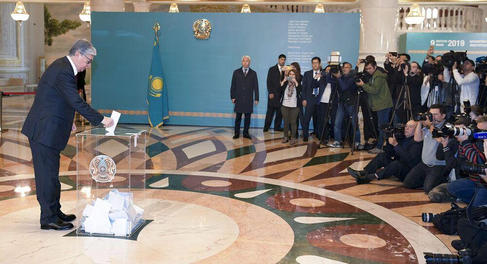 O presidente do Cazaquistão, Kassym-Jomart Tokayev, à esquerda, deposita seu voto em uma seção eleitoral durante as eleições presidenciais em Nur-Sultan, Cazaquistão, em 9 de junho de 2019.