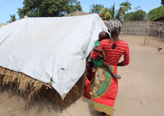 Mulher carrega criança em acampamento de deslocados na província de Cabo Delgado, no norte de Moçambique