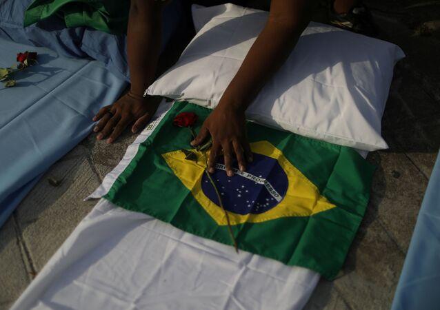 Manifestante coloca bandeira do Brasil em lençol hospitalar, simbolizando as mais de 300 mil vítimas da COVID-19 no país, Rio de Janeiro, 24 de março de 2021