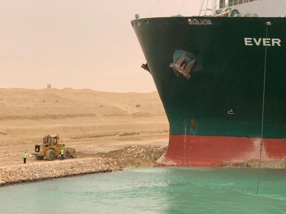 Trabalhadores são vistos ao lado do porta-contêineres que encalhou depois de se desviar da rota devido a ventos fortes no canal de Suez, 24 de março de 2021