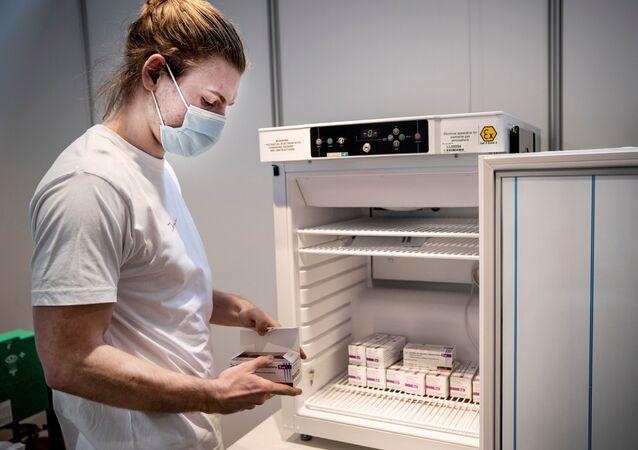 Membro da equipe lida com vacinas da AstraZeneca contra a COVID-19 armazenadas no Centro de Vacinas da Região Hovedstaden, Copenhague, Dinamarca, 11 de fevereiro de 2021.