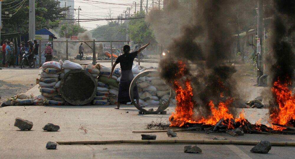 Manifestantes se reúnem atrás de barricadas durante um protesto contra o golpe militar em Mianmar, na cidade de Mandalay, em 22 de março de 2021