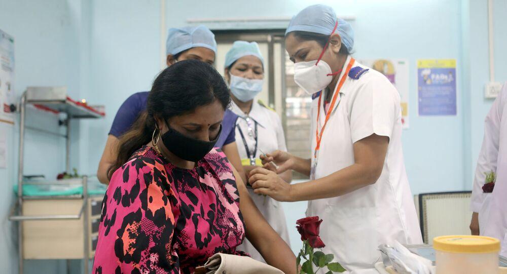 Um profissional de saúde segurando uma rosa recebe a vacina da AstraZeneca, durante campanha de vacinação contra a COVID-19, em um centro médico em Mumbai, Índia, em 16 de janeiro de 2021.