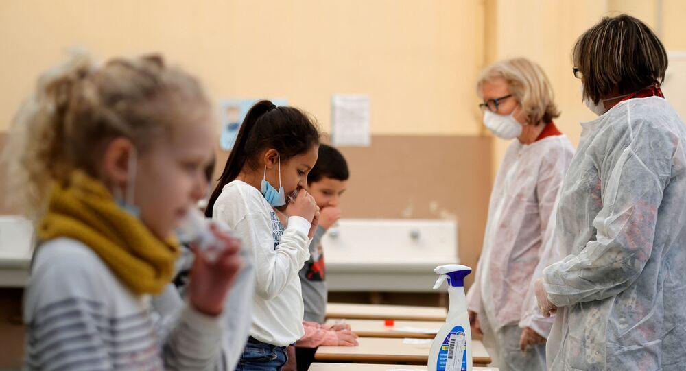 Crianças em idade escolar participam de um teste de saliva pra detecção da COVID-19 em uma escola primária em Nice, França
