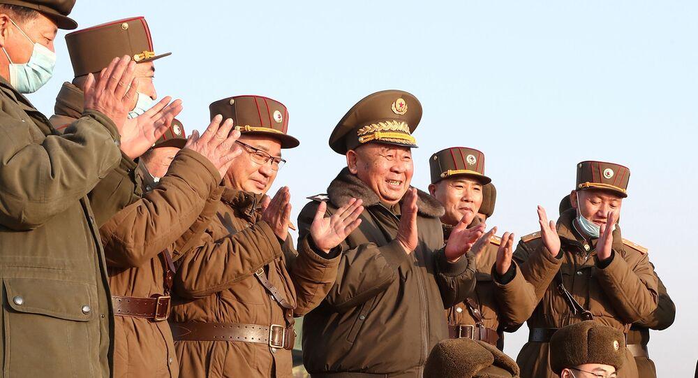 Ri Pyong Chol, líder sênior que está supervisionando testes militares, e outros oficiais aplaudem o lançamento de um novo tipo de projétil guiado tático recentemente desenvolvido, em 25 de março de 2021.