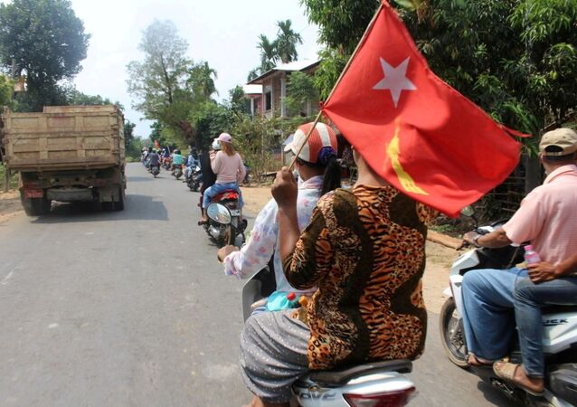 Manifestante sentado em uma motocicleta exibe bandeira durante um protesto em Launglone, distrito de Dawei, Mianmar, em 26 de março de 2021.