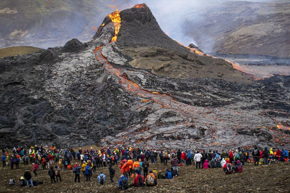 Pessoas assistem a uma erupção vulcânica na Islândia