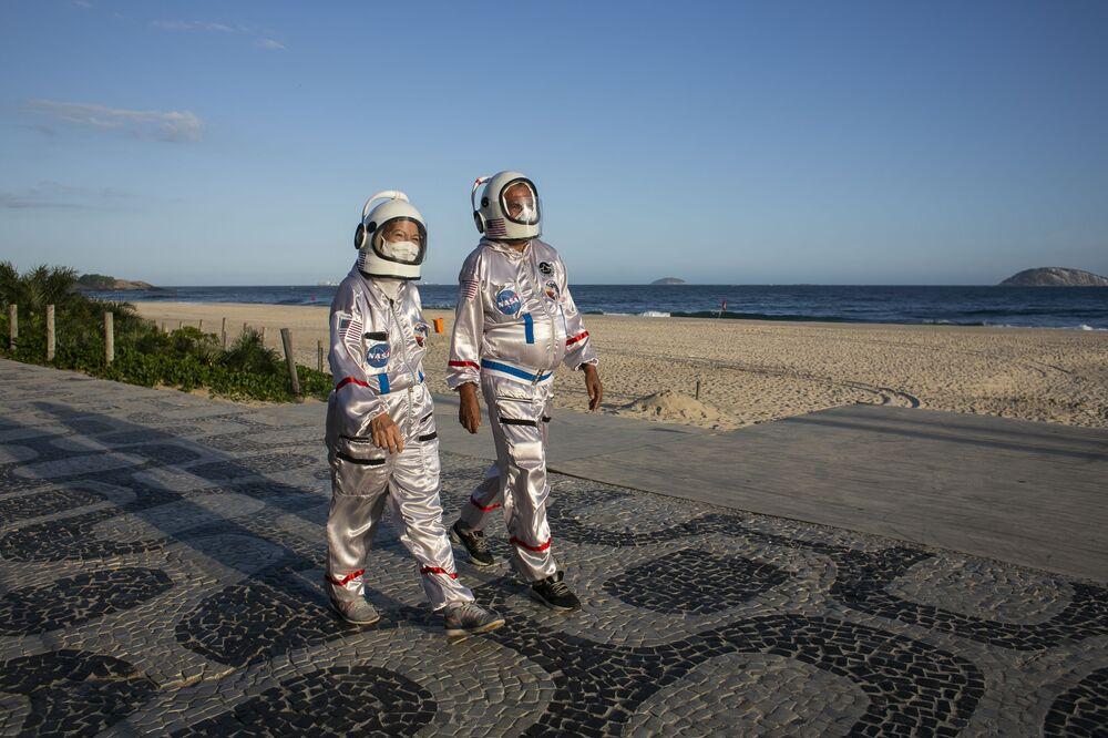 Casal vestido de astronautas caminha pela praia de Ipanema