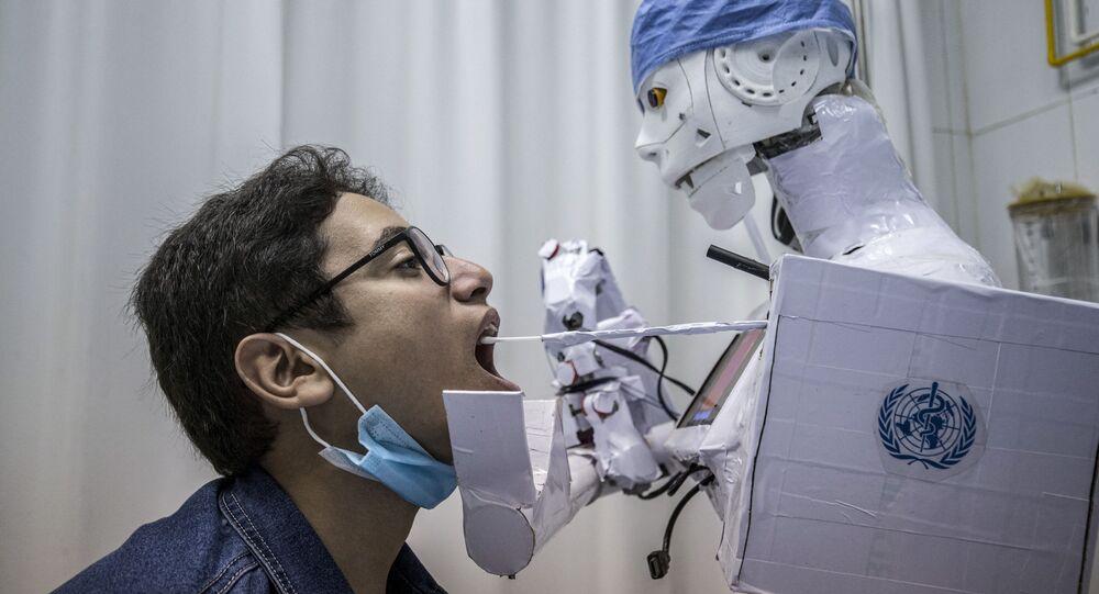 Robô coleta, com um chumaço de algodão, material para fazer análise de COVID-19 em um hospital egípcio