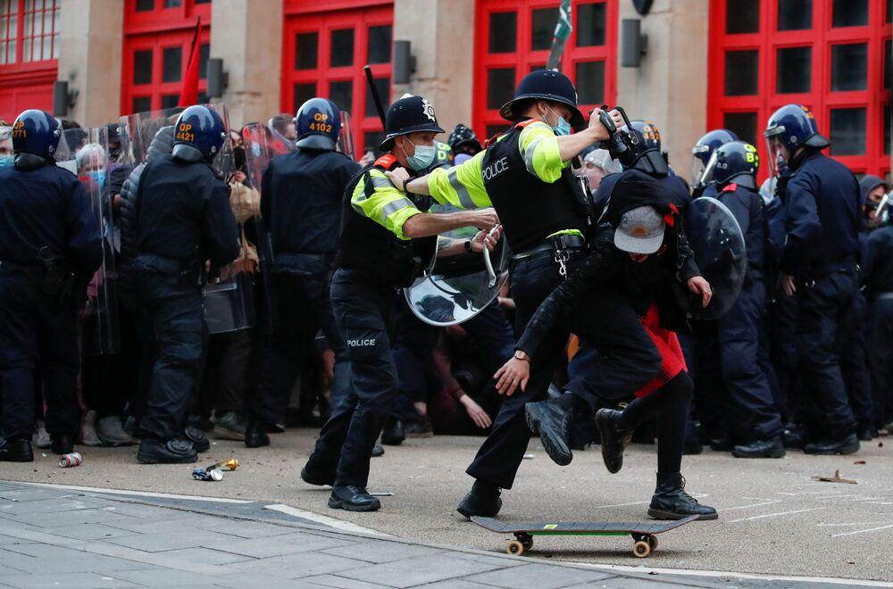 Policial tenta deter um manifestante durante protesto no Reino Unido
