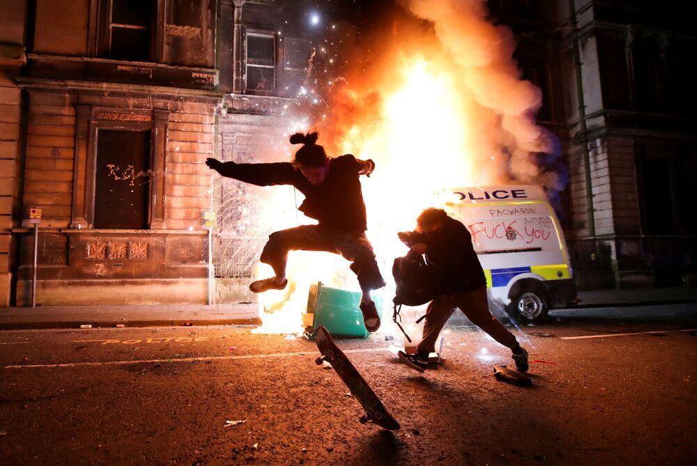 Manifestante anda de skate na frente de um carro da polícia em chamas durante protesto no Reino Unido