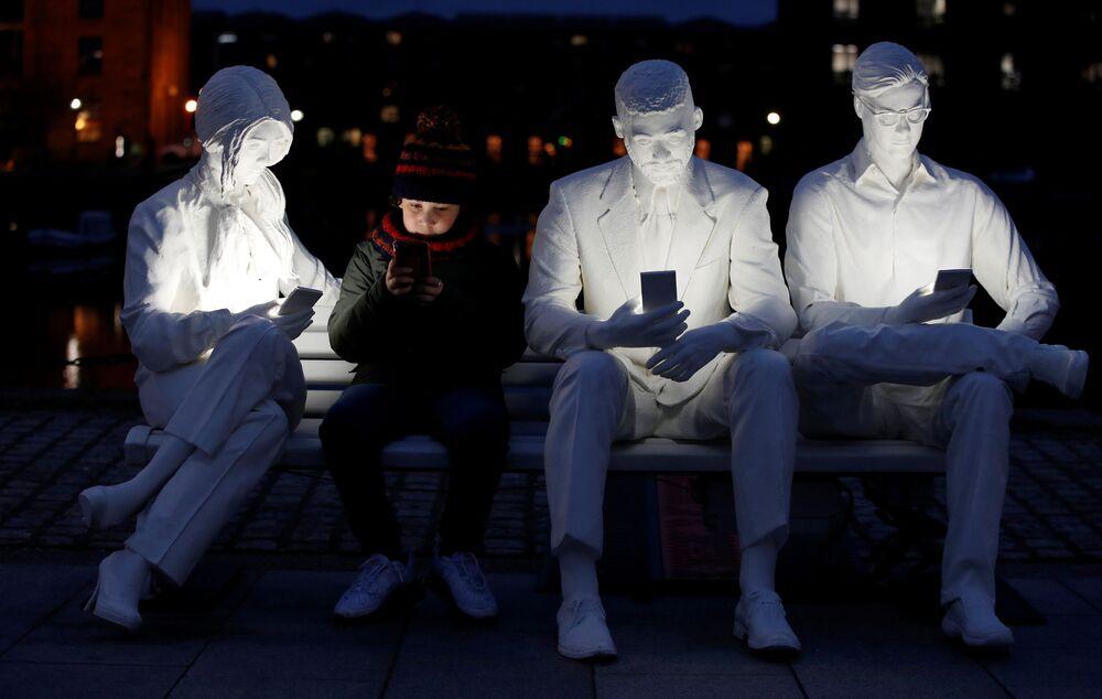 Menino posa com a escultura Absorvido pela Luz em Liverpool, Reino Unido