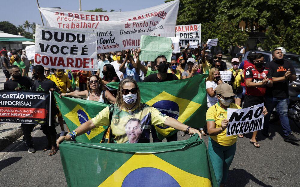 Mulher enverga camisa com foto de Jair Bolsonaro durante protesto no Rio de Janeiro contra novas medidas implementadas para conter a propagação de COVID-19